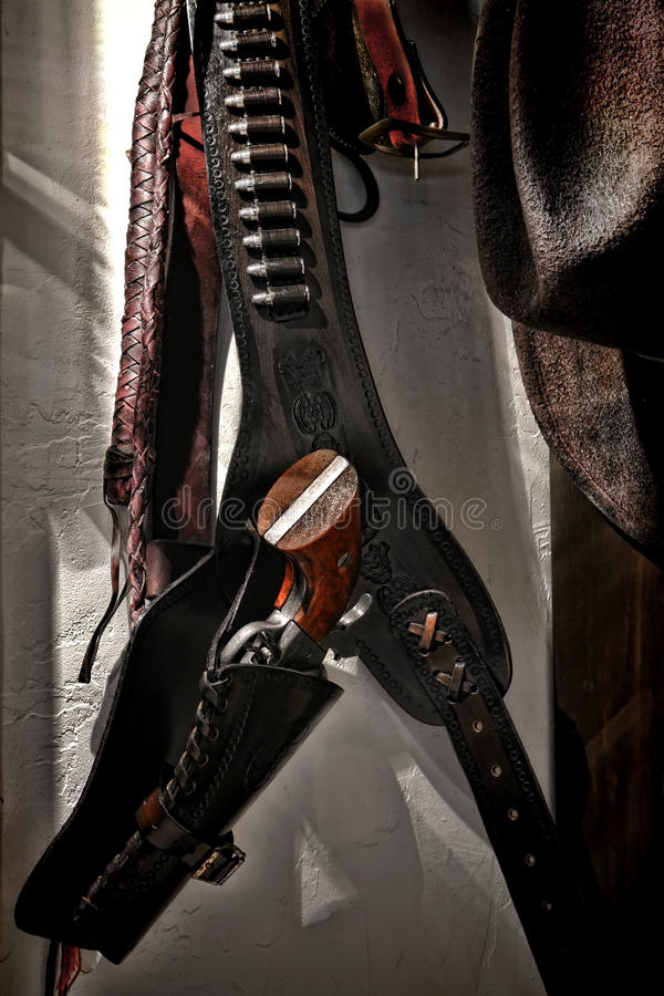 American West Revolver Gun and Holster on Old Wall. American West Legend revolver Peacemaker gun hanging in western leather firearm holster with vintage 45 royalty free stock photos