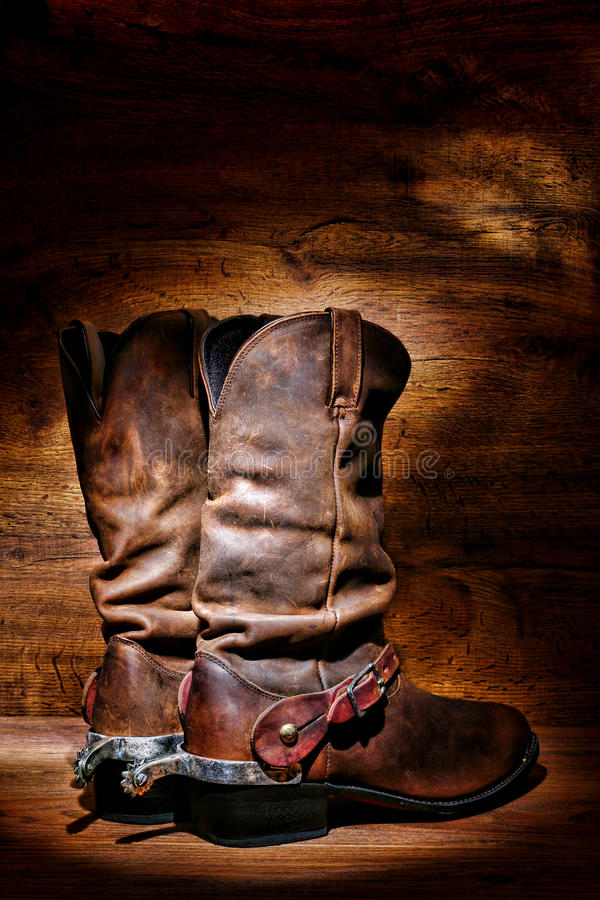 American West Rodeo Cowboy Boots and Western Spurs. American West rodeo cowboy traditional leather boots with authentic Western riding spurs over vintage wood in royalty free stock photos