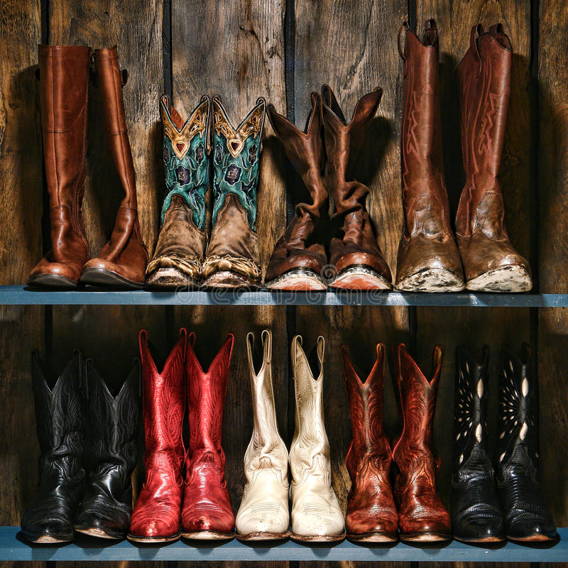 American West Rodeo Cowboy and Cowgirl Boots Shelf. American West rodeo used and worn cowboy and cowgirl leather boots collection stacked on old wood shelf in a stock photo