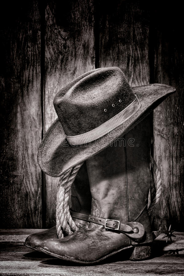 American West Rodeo Cowboy Hat atop Western Boots. American West rodeo cowboy dirty and used black felt hat atop worn and old leather working rancher boots with stock images