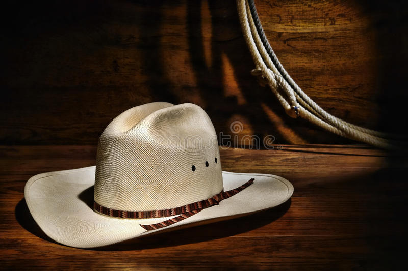 American West Rodeo Cowboy Hat in Old Ranch Barn. American West rodeo authentic cowboy white straw hat and lasso rope in a ranching wood barn royalty free stock image