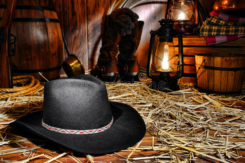 American West Rodeo Cowboy Hat in Old Western Barn. American West rodeo cowboy traditional black felt hat on straw covered wood floor in a vintage ranch barn stock photos