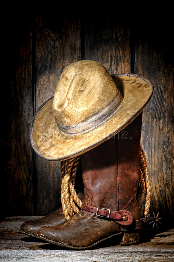 American West Rodeo Cowboy Hat and Western Boots. American West rodeo cowboy dirty and used white felt hat atop worn and muddy leather working rancher boots with royalty free stock photo