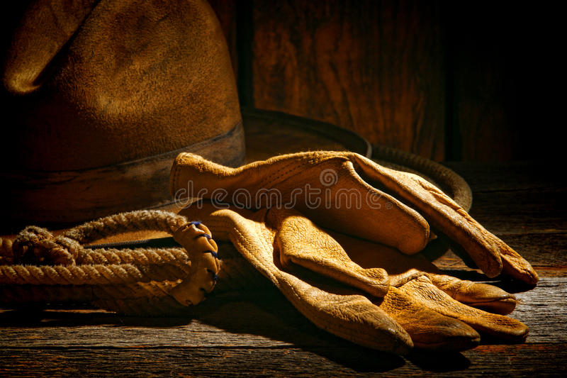 American West Rodeo Ranching Gloves and Cowboy Hat. American West rodeo tough leather ranching gloves on authentic lasso lariat with vintage western cowboy hat royalty free stock photography