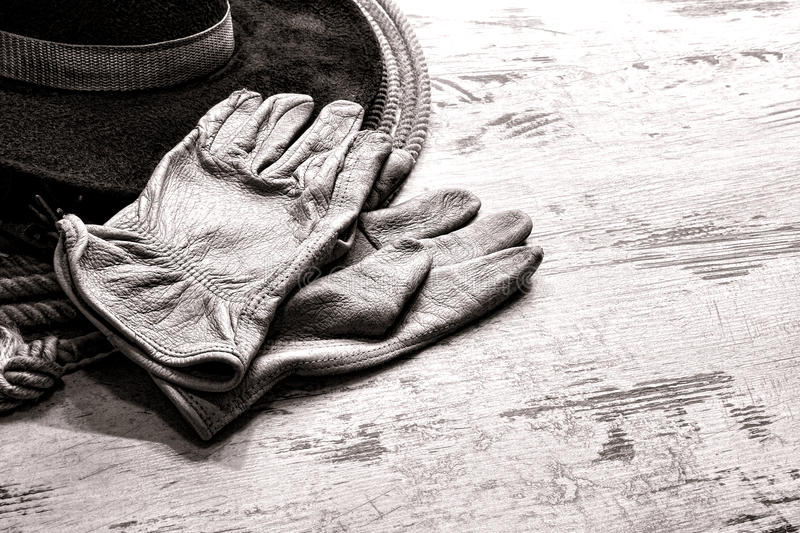 American West Rodeo Ranching Gloves on Western Hat. American West rodeo worn leather ranching gloves on authentic western cowboy hat atop a vintage lasso lariat royalty free stock photography