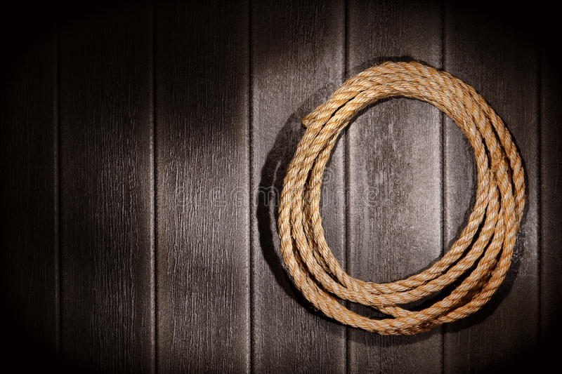 American West Rodeo Rope on Old Rustic Barn Wall. American West rodeo natural hemp fiber rancher rope for ranching and steer roping on grunge vintage barn wood royalty free stock photos