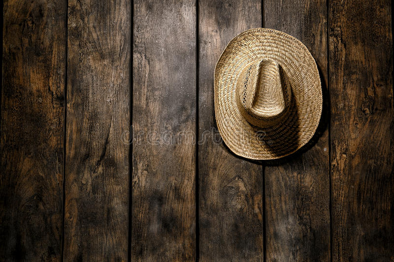 American West Rodeo Straw Hat Hanging on Barn Wall. American West rodeo country farmer traditional straw hat hanging on distressed wood boards wall in a vintage stock images