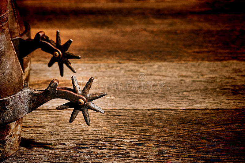 American West Rodeo Vintage Spurs on Cowboy Boots. American West rodeo vintage riding spurs with sharp spikes rowel on authentic western cowboy traditional royalty free stock image