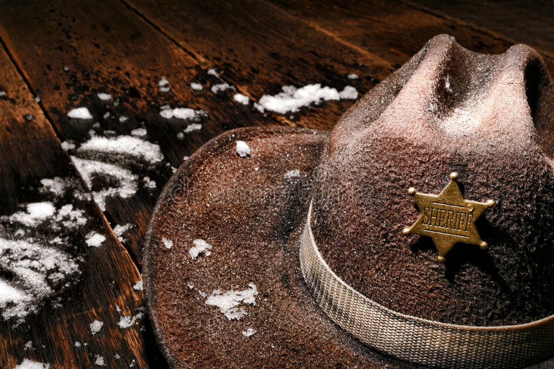 American West Sheriff Badge on Hat and Winter Snow. American West Legend wet and worn vintage lawman cowboy hat with law enforcement sheriff star badge on an royalty free stock image
