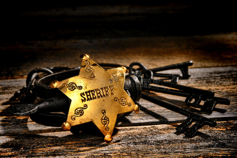 American West Sheriff Star Badge and Old Handcuffs. American West Legend law enforcement officer lawman sheriff deputy brass star badge on a pair of old vintage royalty free stock photo