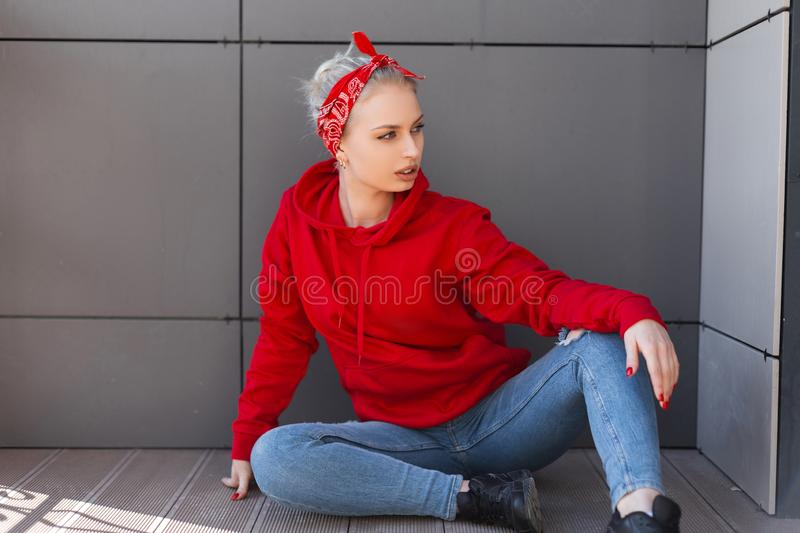 American young blond woman in black boots in a red bandana with a pattern in ripped jeans in a vintage red sweatshirt sitting. Near a gray wall on a summer day stock photography