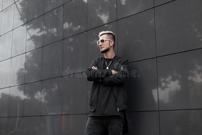 American young hipster man with a fashionable hairstyle with a beard in stylish sunglasses in a trendy black jacket posing royalty free stock photos