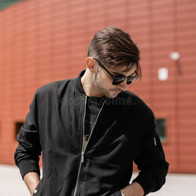 American young hipster man in a stylish black jacket in fashionable sunglasses with a trendy hairstyle relaxes. Near a red modern building on a summer day stock photography