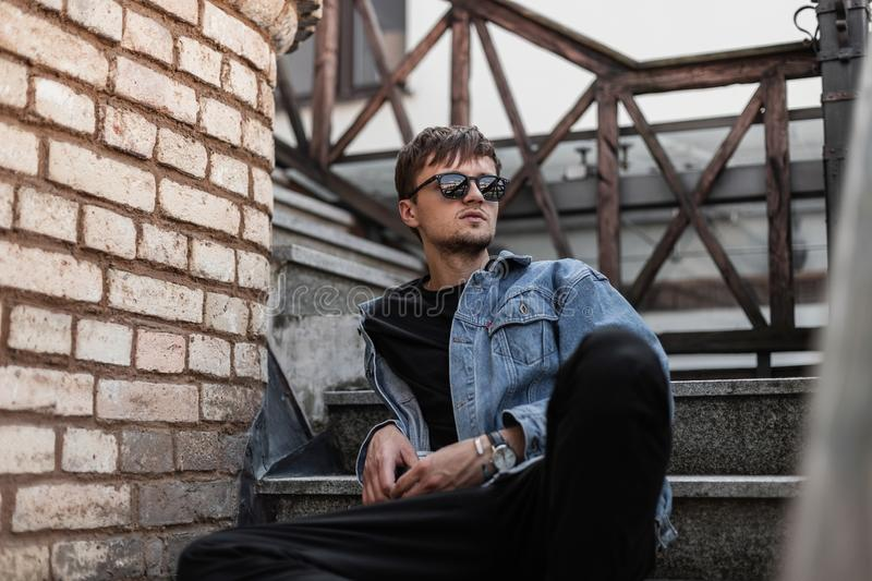 American young man hipster in a blue denim jacket in trendy pants in stylish black sunglasses relaxes near brick wall. On a vintage staircase in the street on a stock images