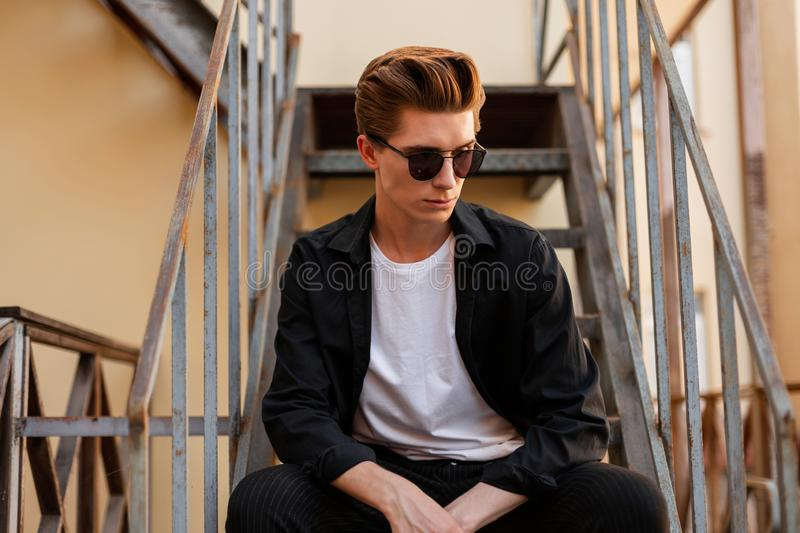American young man hipster in an elegant shirt in a t-shirt in trendy sunglasses sits on an iron staircase in the city. royalty free stock image