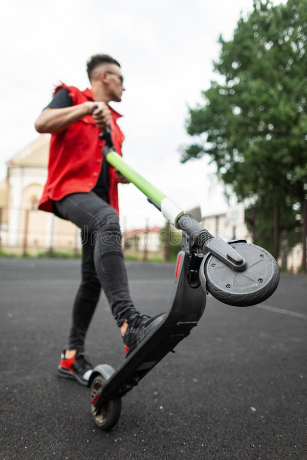 American young man rides an modern electric scooter. Cool fashionable hipster guy in stylish jeans clothes in sunglasses posing. With electric scooter on the stock photo