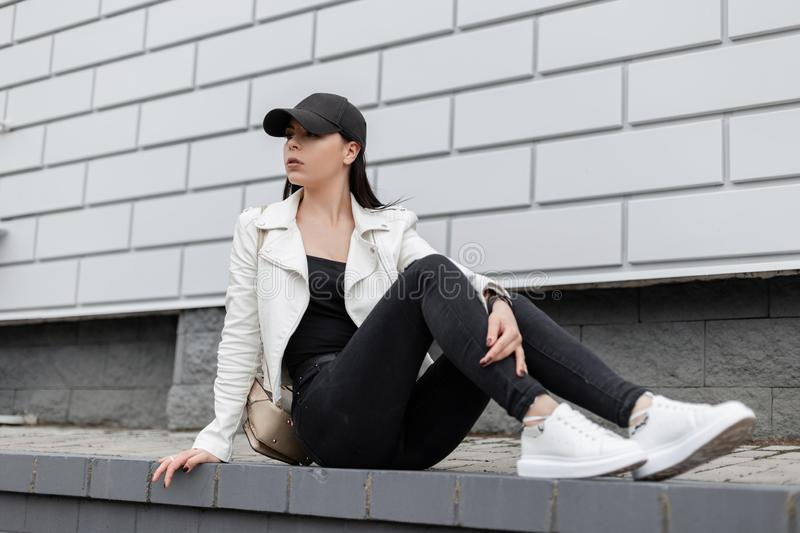 American young woman in a jacket in leather sneakers in black jeans in a stylish baseball cap with a backpack sits on a tile. Near a vintage building in the stock image