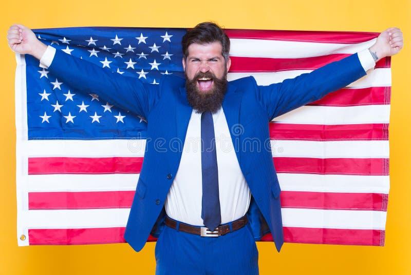 Americano dalla nascita Ribelle dalla scelta Uomo barbuto bello dell'uomo d'affari sicuro in bandiera convenzionale U.S.A. della  fotografia stock