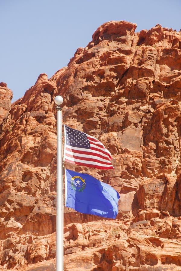 Americano e bandeira de Nevada na frente da rocha vermelha imagens de stock