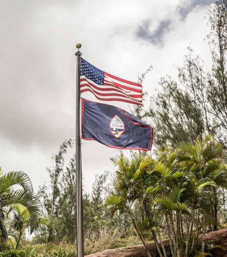 Americano e bandeiras de Guam com as palmeiras no fundo fotografia de stock