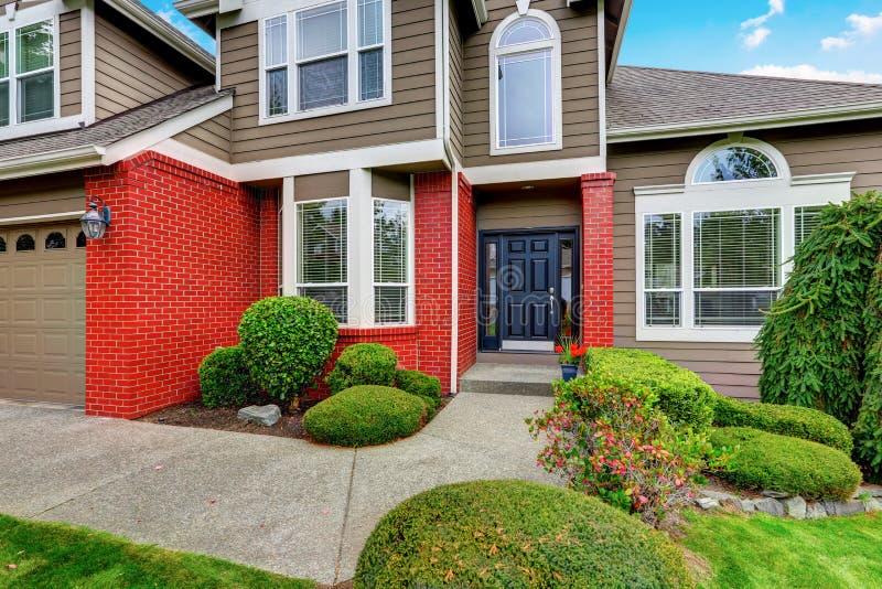 Amerikaans beige huis met rode baksteenversiering en donkerblauwe voordeur stock foto's