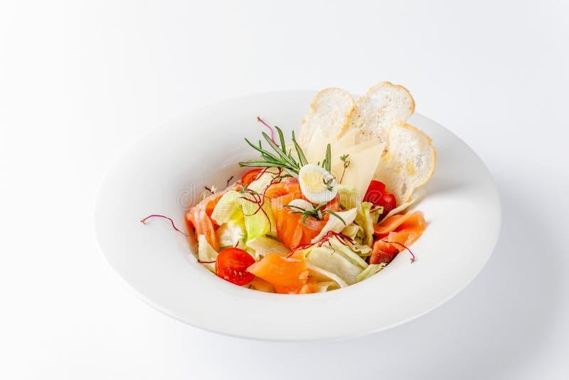 Amerikaans keukenconcept De Salade van Caesar met Zalm Witte plaat op een witte achtergrond Beeld voor een menu van restaurants stock foto