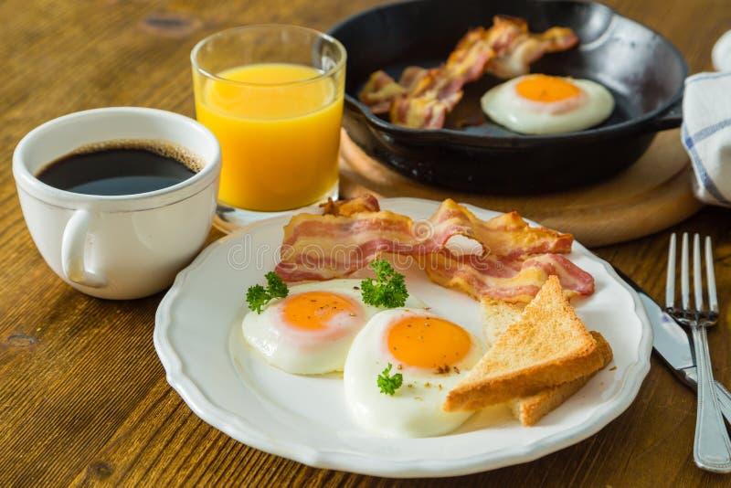 Amerikaans ontbijt met zonnige kant op eieren, bacon, toost, pannekoeken, koffie en sap royalty-vrije stock afbeeldingen