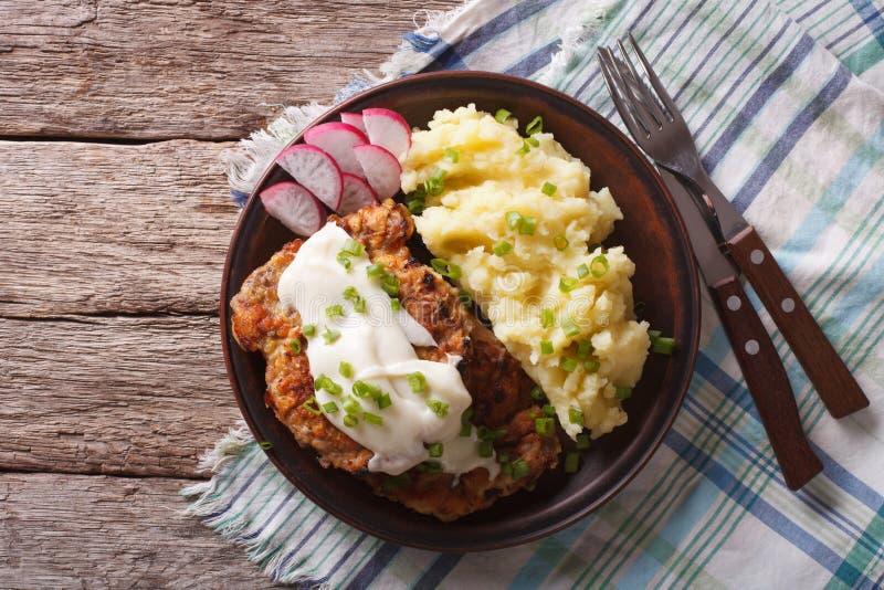 Amerikaans voedsel: Land Fried Steak en Witte Jus horizontaal aan stock foto