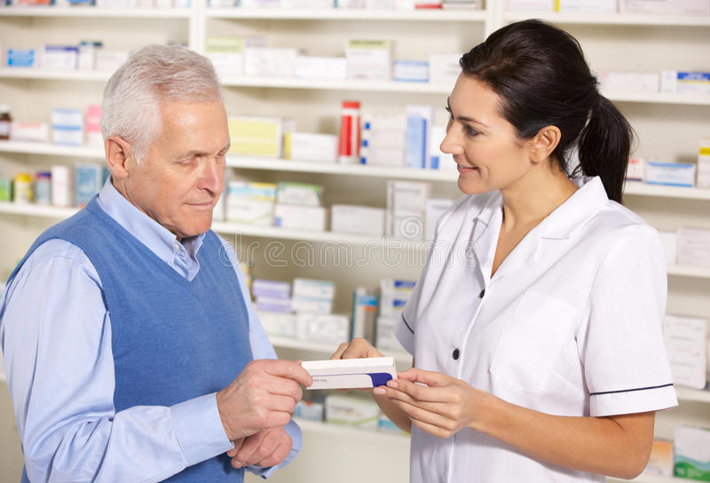 Amerikaanse apotheker die de hogere mens in apotheek dient stock foto