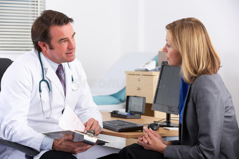 Amerikaanse arts die aan onderneemsterpatiënt spreekt stock foto's
