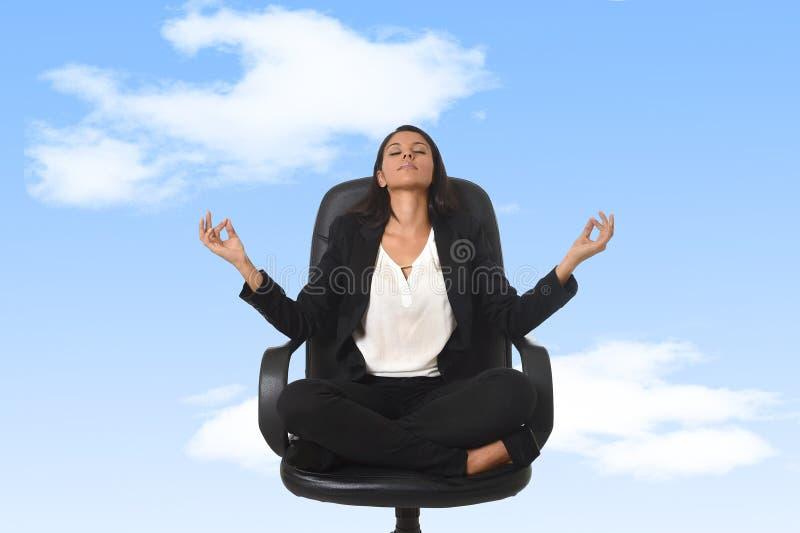 Amerikaanse bedrijfsvrouwenzitting bij bureaustoel in lotusbloemhouding het praktizeren yoga en meditatie