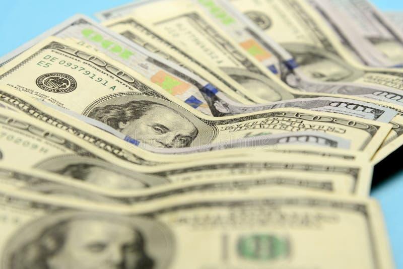 Amerikaanse 100 die dollarrekeningen op een blauwe achtergrond worden opgemaakt stock afbeeldingen