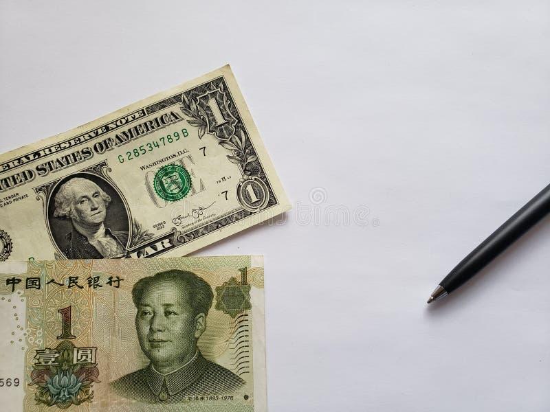 Amerikaanse dollarrekening, Chinees bankbiljet van één yuan, zwarte pen en witte achtergrond stock foto