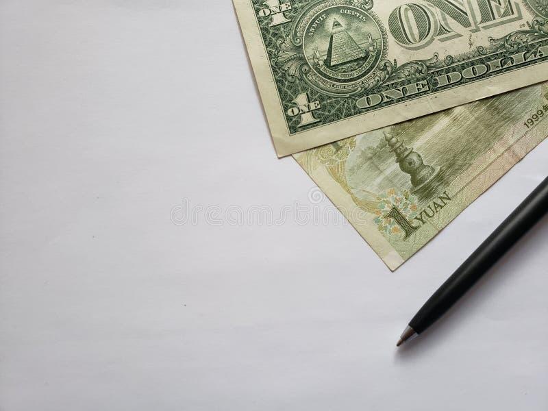 Amerikaanse dollarrekening, Chinees bankbiljet van één yuan, zwarte pen en witte achtergrond royalty-vrije stock foto