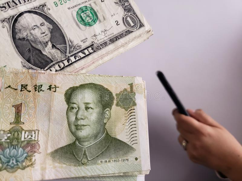 Amerikaanse dollarrekeningen, Chinese bankbiljetten en hand die een smartphone houden stock foto's