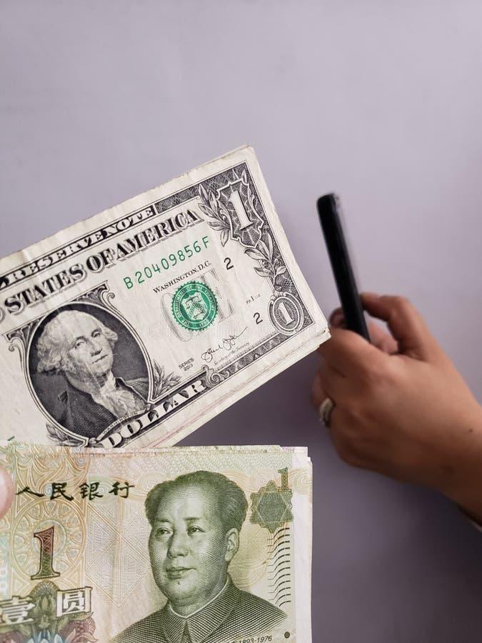 Amerikaanse dollarrekeningen, Chinese bankbiljetten en hand die een smartphone houden stock afbeeldingen
