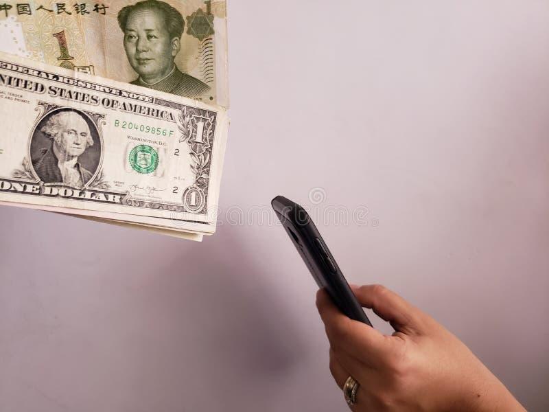 Amerikaanse dollarrekeningen, Chinese bankbiljetten en hand die een smartphone houden stock fotografie