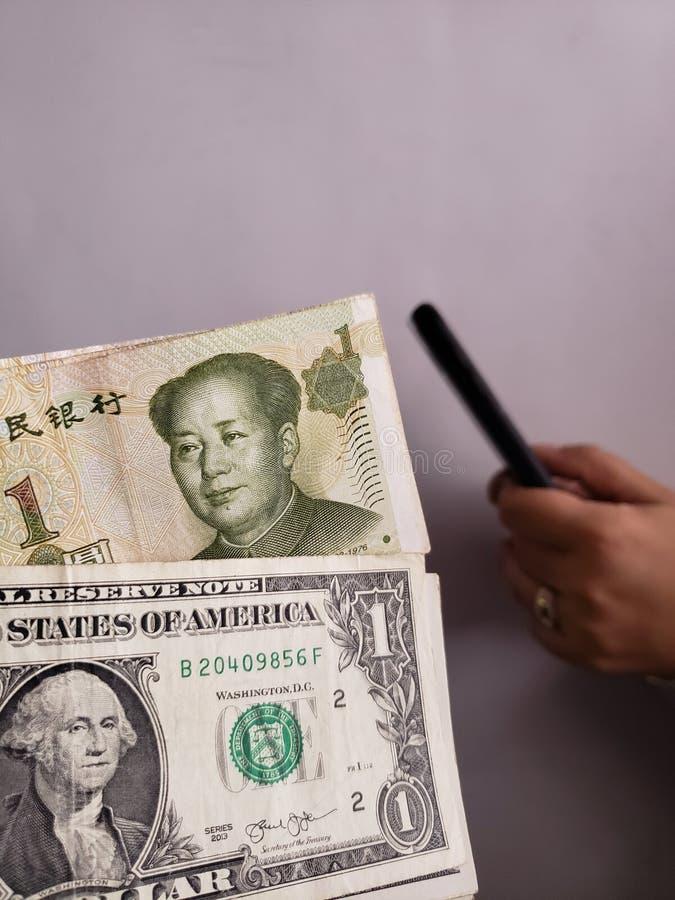 Amerikaanse dollarrekeningen, Chinese bankbiljetten en hand die een smartphone houden royalty-vrije stock fotografie