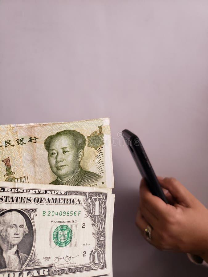 Amerikaanse dollarrekeningen, Chinese bankbiljetten en hand die een smartphone houden royalty-vrije stock foto's