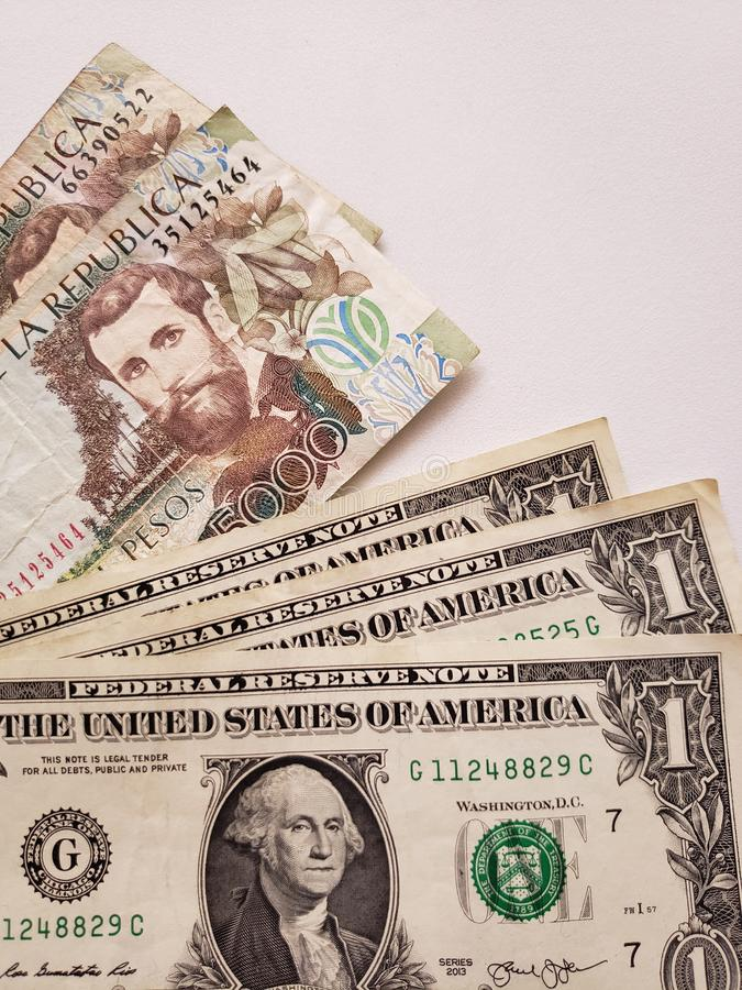Amerikaanse dollarrekeningen en Columbiaanse bankbiljetten van 5000 peso's royalty-vrije stock fotografie