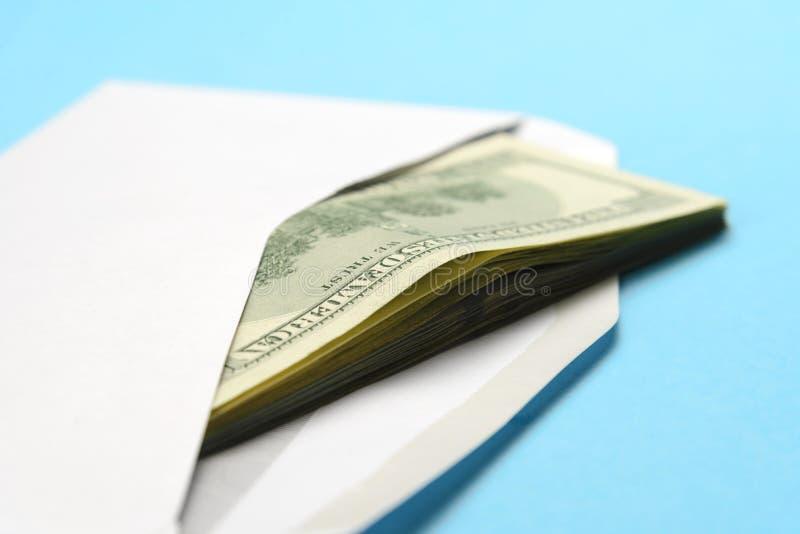 Amerikaanse dollars in open witte postenvelop op een blauwe achtergrond stock afbeeldingen