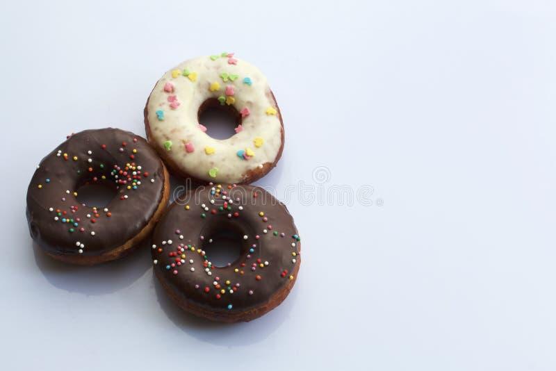 Amerikaanse donuts, die met gesmolten chocolade wordt verglaasd en die met het bestrooien wordt verfraaid, liggen op een witte ac stock foto