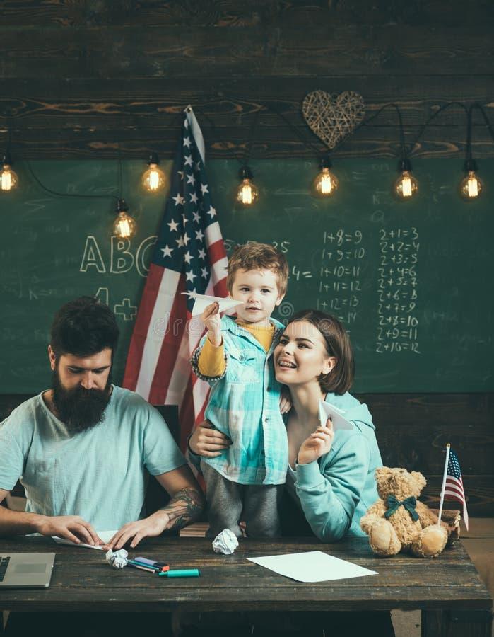 Amerikaanse familie bij bureau met zoon die document vliegtuigen maken Ouders die zoon het Amerikaanse tradities spelen onderwijz stock afbeeldingen