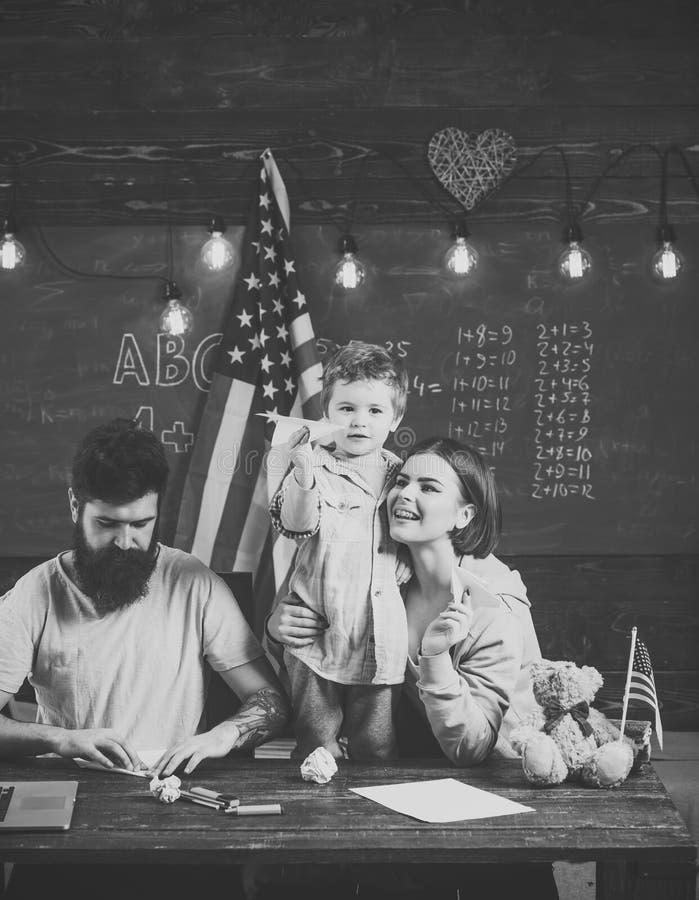 Amerikaanse familie bij bureau met zoon die document vliegtuigen maken Ouders die zoon het Amerikaanse tradities spelen onderwijz royalty-vrije stock afbeelding