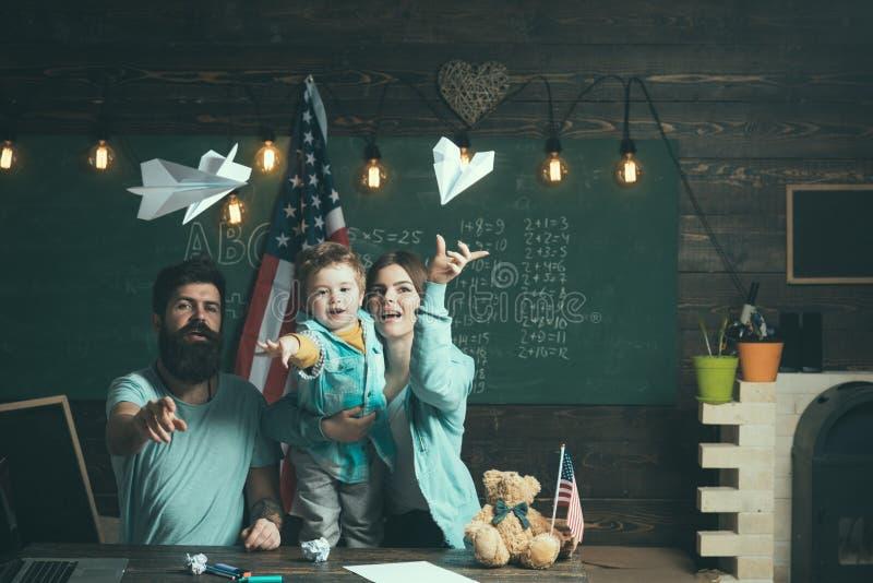 Amerikaanse familie bij bureau met zoonsspel met document vliegtuigen Homeschoolingsconcept Jong geitje met ouders in klaslokaal  royalty-vrije stock foto's