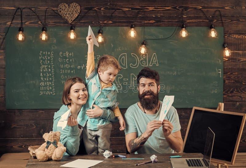 Amerikaanse familie bij bureau met zoonsspel met document vliegtuigen Homeschoolingsconcept Ouders die zoon Amerikaanse tradities stock foto