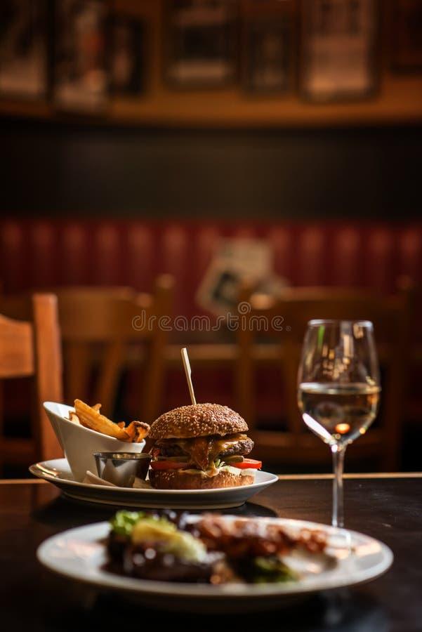 Amerikaanse hamburger met glas bier of wijn in restaurant, bier, hamburger, wijn en andere Amerikaanse specialites royalty-vrije stock afbeeldingen