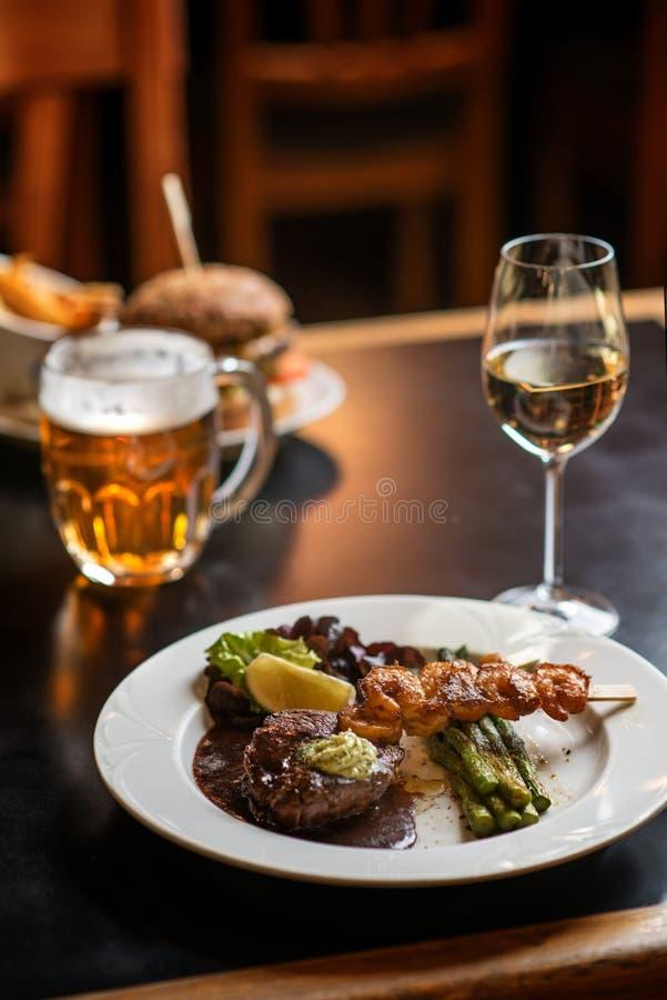 Amerikaanse hamburger met glas bier of wijn in restaurant, bier, hamburger, wijn en andere Amerikaanse specialites royalty-vrije stock foto's
