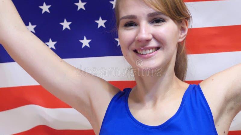 Amerikaanse Jonge Vrouw die terwijl het houden van de vlag van Amerika in Langzame Motie vieren stock foto's