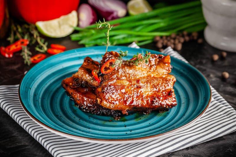 Amerikaanse Keuken Geroosterde gemarineerde varkensvleesribben op een blauwe plaat met garnalen en kruidige Spaanse peper in barb royalty-vrije stock foto